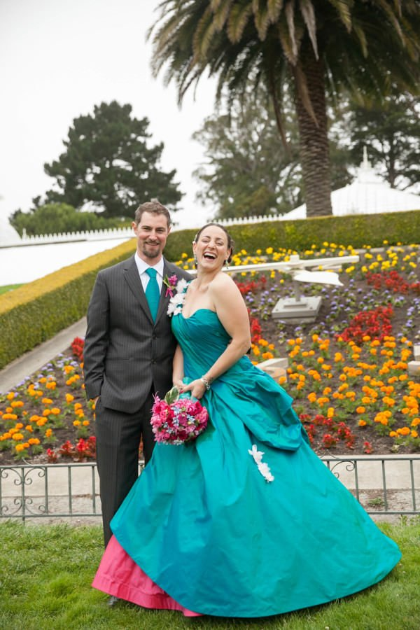 Lavinia wears a bright teal and hot pink, full-skirted bridal gown.