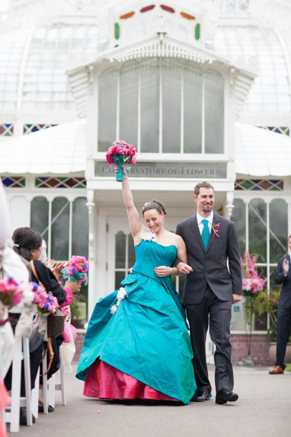 The full skirt of the gown is made more dramatic with additional tucks, ruffles and a hot pink underskirt.