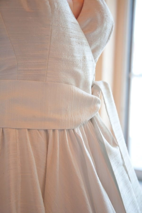 A wide belt at the waist finishes the wrap detail of the bodice.