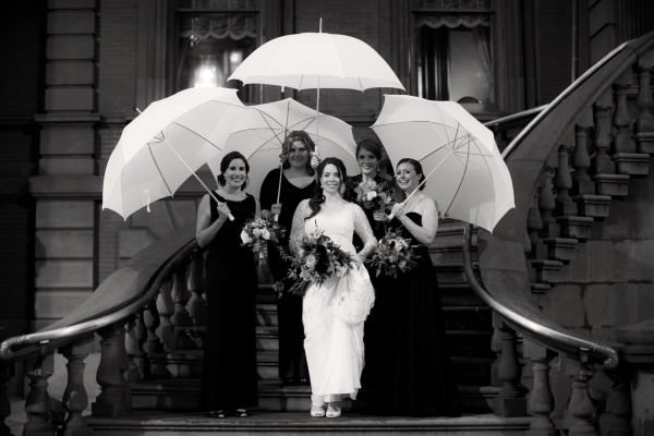 The bride and her bridesmaids avoid the rainy weather on the steps of the Union League in Philadelphia.