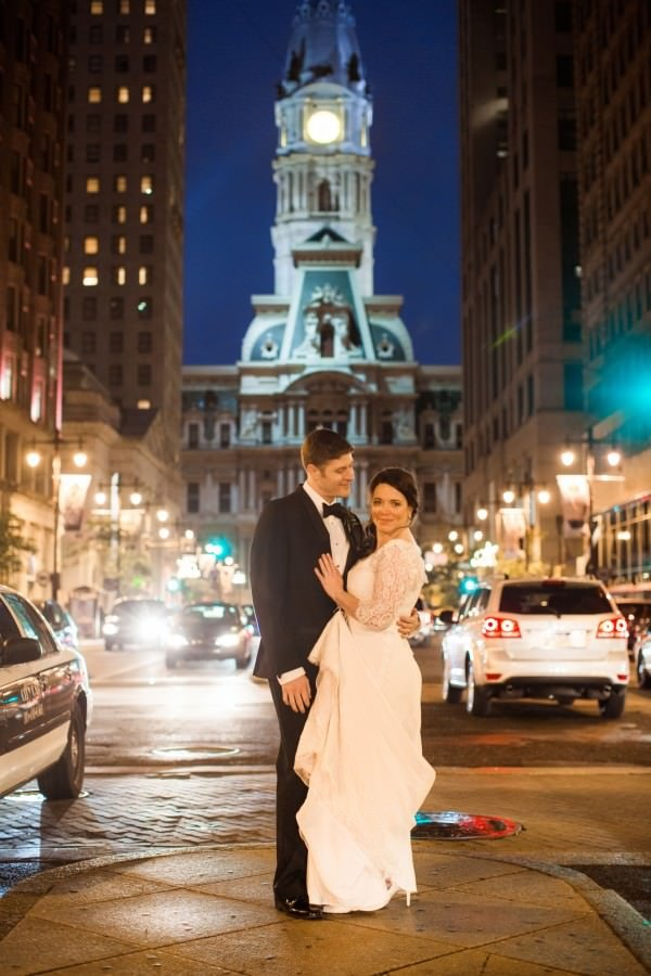 The bride and groom embrace underneath City Hall in Philadelphia.