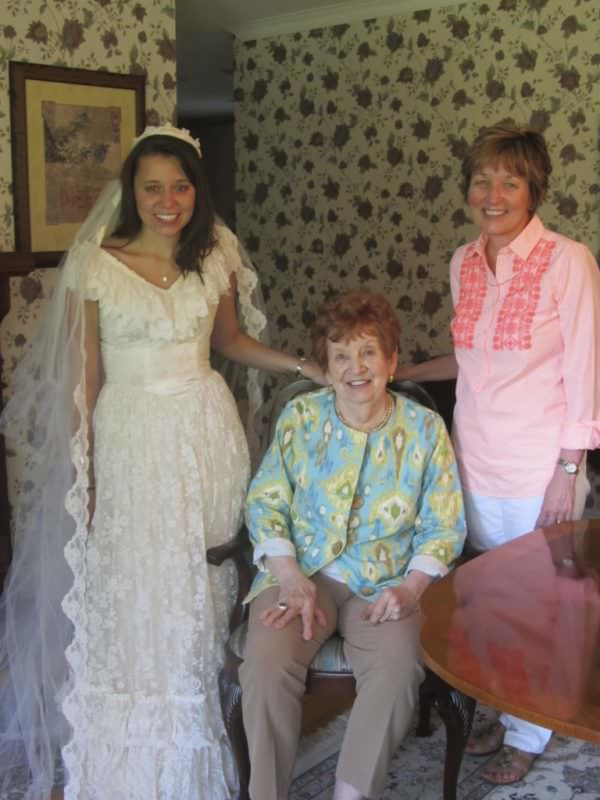 The bride poses in the gown before its recreation with her mother and grandmother.